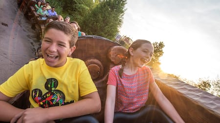 A boy and girl laugh with excitement as they careen down a hill in a theme park roller coaster