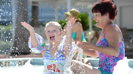 A grandmother and granddaughter in a swimming pool laugh as the little girl splashes water