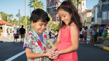 A brother and sister hold a Tinker Bell statuette while standing in Disney's Hollywood Studios