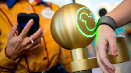 A Guest scans her MagicBand at one of the Park entrances as a Cast Member stands by