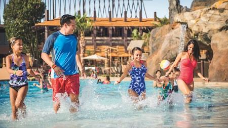 Una familia de 5 camina a orillas de la piscina tipo playa en un Hotel de Disney.