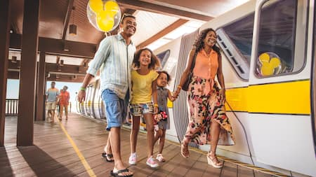 A mom, dad and 2 daughters laugh while walking with a Mickey balloon at the monorail station