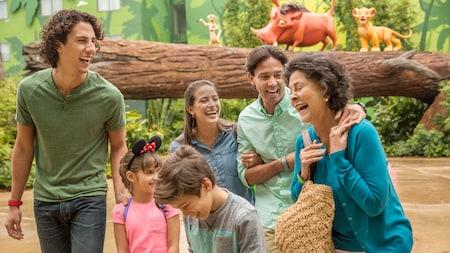 Una familia de 6 se ríe mientras pasa por un tronco de árbol horizontal donde se sientan Timon, Pumba y Simba.