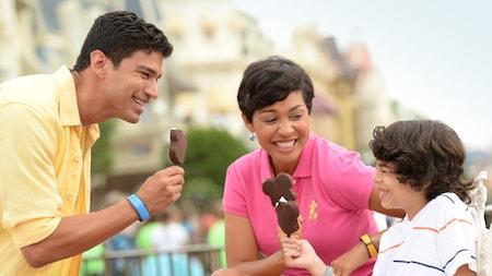 Una mamá, un papá y su hijo sonríen juntos mientras comen las barras de helado de Mickey en el Parque Temático Magic Kingdom