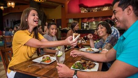 Una mujer ofrece a su esposo un bocado de su sándwich mientras disfrutan con su familia en un concurrido restaurante.