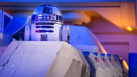R2-D2 pops up from his position inside a craft within a dramatically lit room