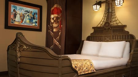 The interior of a pirate themed room with a bed shaped like a ship and pirate inspired decor