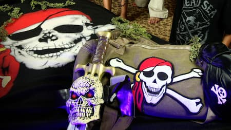 A sword with an angry looking skeleton head rests upon a duffel bag adorned with a large skull and crossbones patch