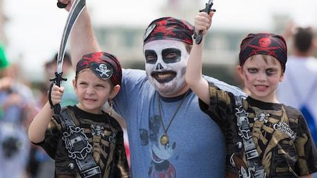 Pai com maquiagem de caveira e bandana e filho fantasiado de pirata levantam espadas de brinquedo