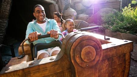 Una familia sonríe mientras disfruta un paseo en el Seven Dwarfs Mine Train en el Parque Temático Magic Kingdom