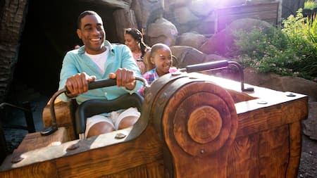 A family smiles while riding Seven Dwarfs Mine Train at Magic Kingdom park