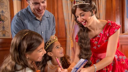 Princess Elena smiles while holding out her scepter to a young girl dressed in a tiara and princess costume