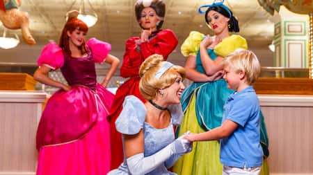 Cinderella kneels to talk with a little boy, and her stepmother and 2 ugly stepsisters grimace