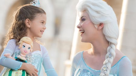 Elsa from Disney's Frozen talks with a little girl who is dressed like her and holds an Elsa doll