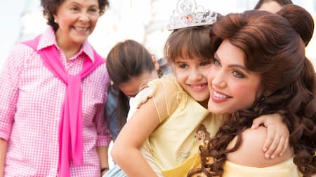 Belle hugs a little girl dressed as a Belle princess, with her grandmother looking on