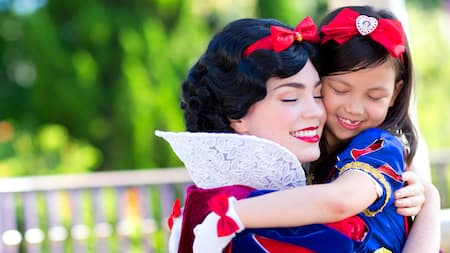 Snow White holds a little girl in her arms who is dressed in a Snow White costume
