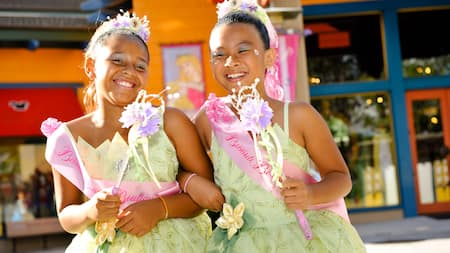 Two smiling girls dressed as identical princesses wear ribbons that read 'Bibbidi Bobbidi Boutique'