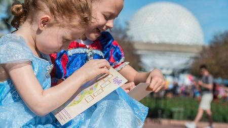 2 jóvenes Visitantes con vestidos de princesa dibujan en mapas de Epcot, con Spaceship Earth en el fondo.