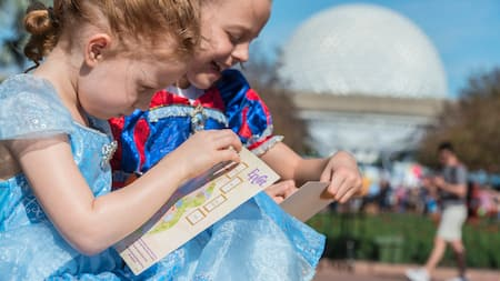 2 young Guests in princess attire, drawing on maps of Epcot with Spaceship Earth in the background