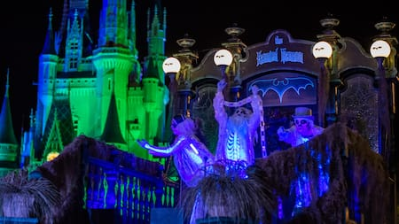 Cinderella Castle looms in the background of 3 ghoulish ghosts standing under a sign that reads The Haunted Mansion