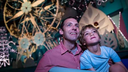 "A father and son watch in wonder while cruising through ""it's a small world"" at Magic Kingdom park"