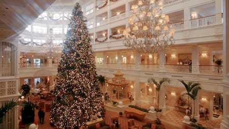 A 3-story Christmas tree towers amid opulent chandeliers inside the lobby of a Disney Resort hotel