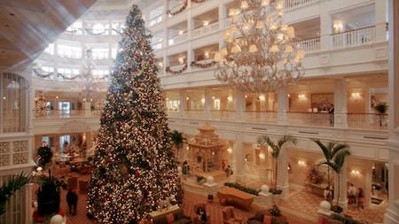 Un arbre de Noël d'une hauteur de trois étages s'élève entre des lustres somptueux à l'intérieur du hall d'un hôtel Disney