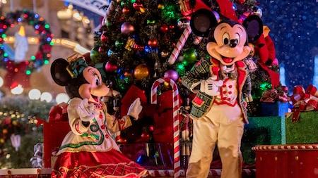 O Mickey e a Minnie Mouse com trajes festivos ao lado de uma árvore de Natal