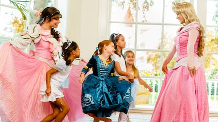 Four young girls practice their curtseys with Princess Aurora and Miss Rose Petal at Disney's Perfectly Princess Tea