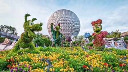 Arbustos artísticos con las formas de Mickey, Minnie, Goofy y Pluto exhibidos justo frente a Spaceship Earth
