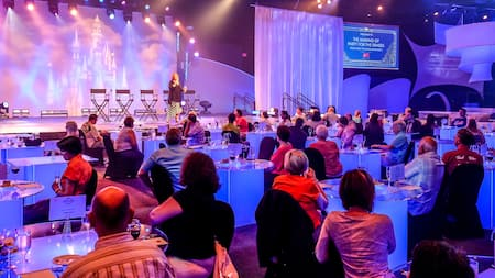 A woman speaks on a stage while an audience seated at tables with glasses of wine and small plates of food listens. Over the stage, a sign reads The Making of Party for the Senses, from idea to implementation