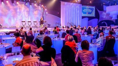 """Mulher apresenta uma palestra no palco, diante de uma plateia sentada às mesas, com taças de vinho e pratinhos de comida. Sobre o palco, uma faixa em que se lê """"Como preparar uma festa para todos os sentidos, da ideia à implementação"""", em inglês"""