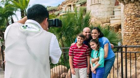 Una familia posa frente a un castillo mientras un fotógrafo de Disney Photo Pass toma una foto