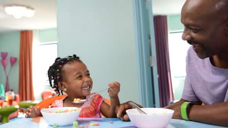 A father and his daughter laugh while enjoying a cereal breakfast together at a Disney Resort hotel