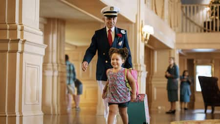 A young girl smiles gleefully as an elderly Cast Member carries her bag at Disney's Yacht Club Resort
