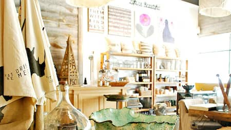 A shop displaying home décor items, art prints and shelves of pillows and glass trinkets