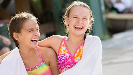Two laughing young Guests in swimwear are wrapped in a towel together