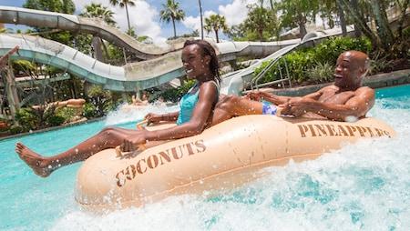 2 jovens Visitantes dividem um bote inflável em uma atração de Parque Aquático