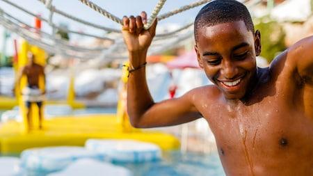 Um jovem Visitante segurando uma corda para se apoiar em um percurso de obstáculos em um Parque Aquático