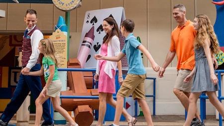 Uma família animada sorri enquanto segue um empolgado guia VIP Tour até a Toy Story Midway Mania