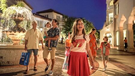 Una familia mira con asombro un área estilo aldea con una fuente en el centro
