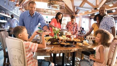 Una familia disfruta una comida en Chef Art Smith's Homecoming mientras un camarero sirve un plato de comida en la mesa