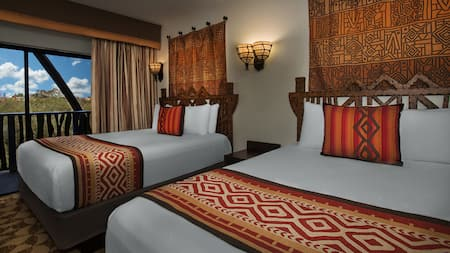 2 queen sized beds in a hotel room with a southwest design