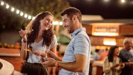A woman and a man share a laugh as they stand and eat dessert at night