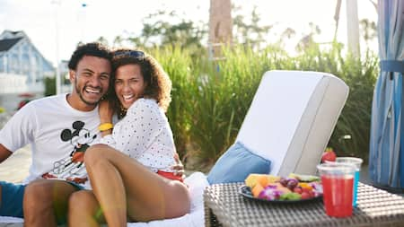 A smiling couple enjoys refreshments while sitting on a cabana lounge chair.