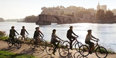 A group of 6 Adventurers follow an Adventure Guide on a bike ride down a bike path along the Rhône River