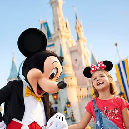 Mickey Mouse and little girl in front of Cinderella's Castle