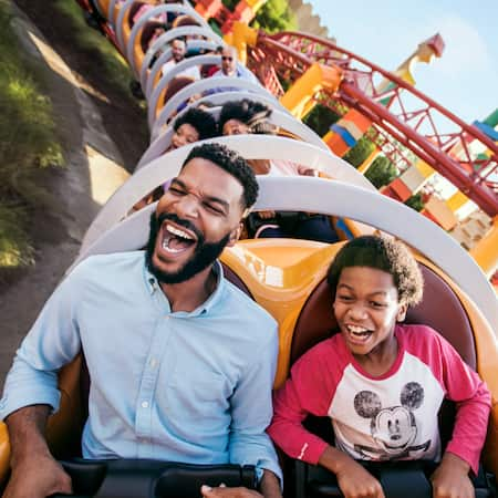A father and son riding on the Slinky Dog Dash coaster in Toy Story Land