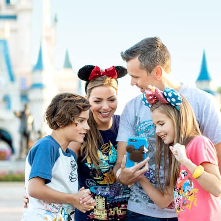 A family looks at a cellphone with a Disney cover in front of Cinderella Castle
