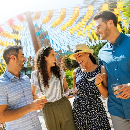 A group of smiling people stand in a huddle outside while holding drinks and food